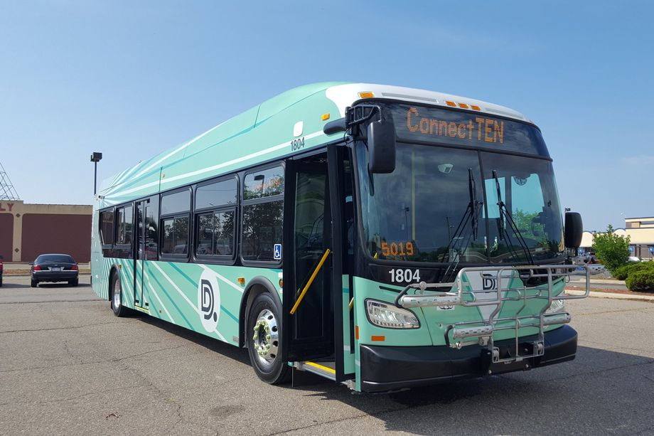 An image of a new DDOT bus outside. It has a light green wrap with bright rays emanating from the back of the bus